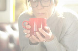 blowing on a hot mug of coffee