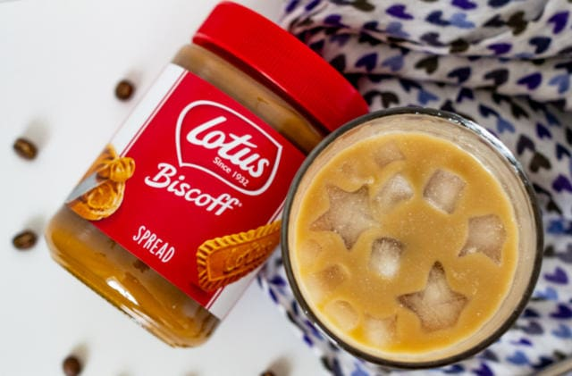 Iced latte from above with jar of Biscoff spread on blue cloth