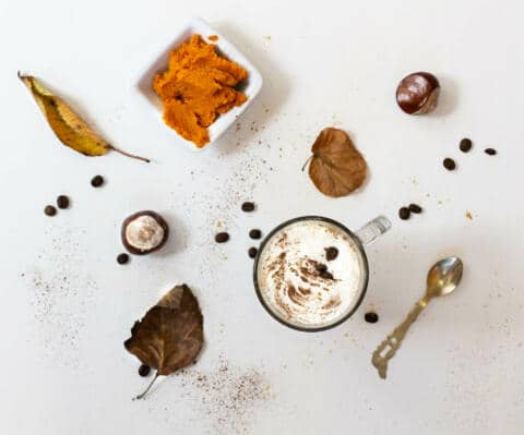 Overhead shot of pumpkin spice latte with dish of pumpkin puree, leaves, conkers and a teaspoon